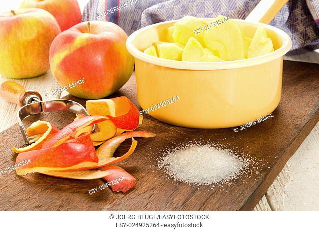 fresh and sliced apple pieces and sugar on wooden board to make apple compote
