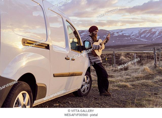 Iceland, young man leaning on van and playing guitar
