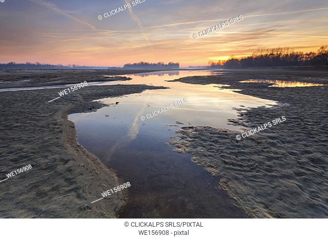 Po river park, Italy. Creeks in the sand with the reflection of a coloured winter sunset