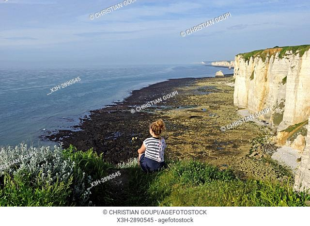 young girl watching ocean sitting on the top of the cliffs of Etretat, Seine Maritime department, Normandie region, France, Europe