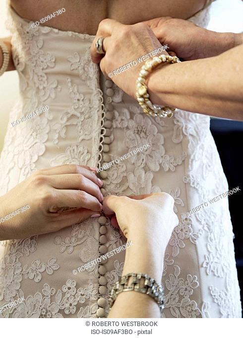 Bride being helped to get into wedding dress