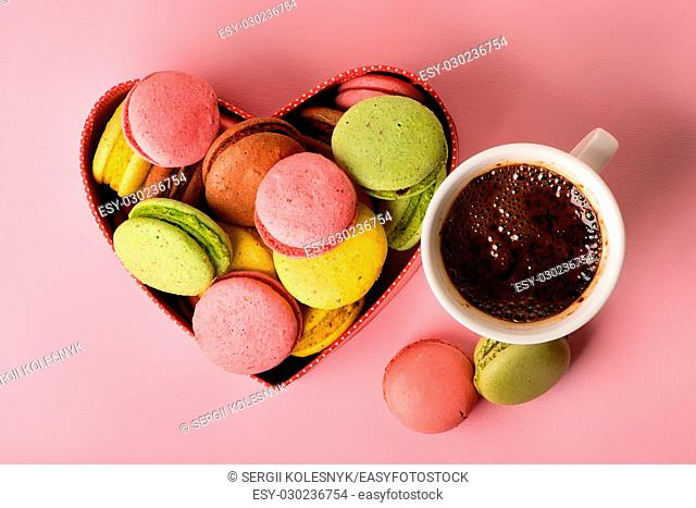 Macarons in gift box with a cup of coffee on pink background