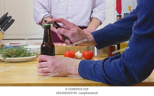 Hand, reaching for a beer bottle, and opening it, with a chef, preparing dinner in the background