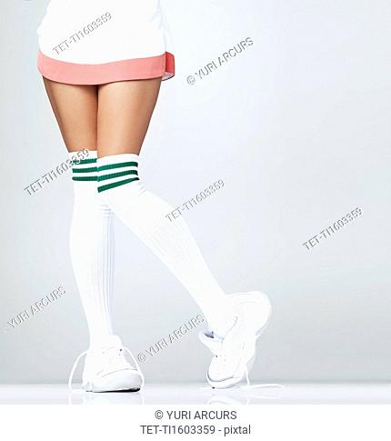 Low section of woman wearing sneakers and knee-high socks