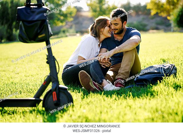 Happy couple with electric scooter relaxing on a meadow in a park