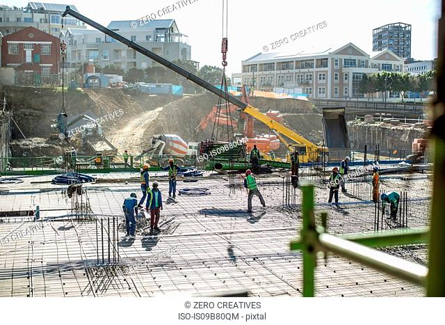 Construction workers laying foundation of building