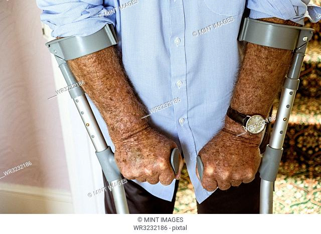 A man using crutches, with his weathered hands on the handles
