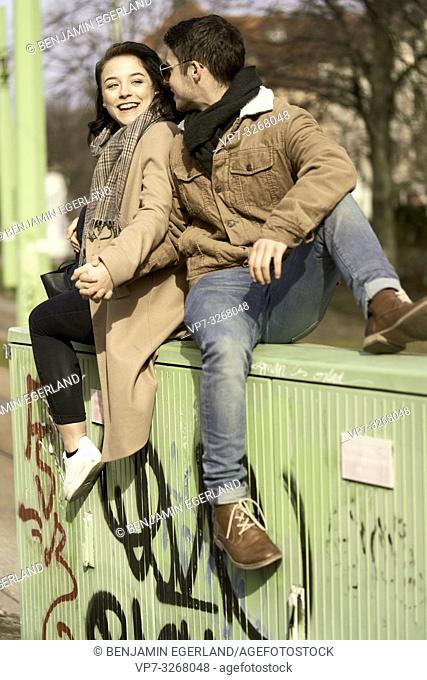 young teenage couple sitting on electricity distribution board in city, in Cottbus, Brandenburg, Germany