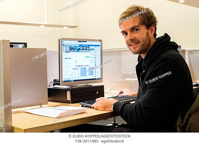Tilburg, Netherlands. Young adult caucasian man working behind a public library computer roaming the Internet