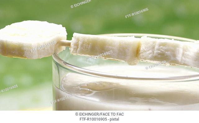 Banana slices pierced into a stick is placed on a banana milkshake