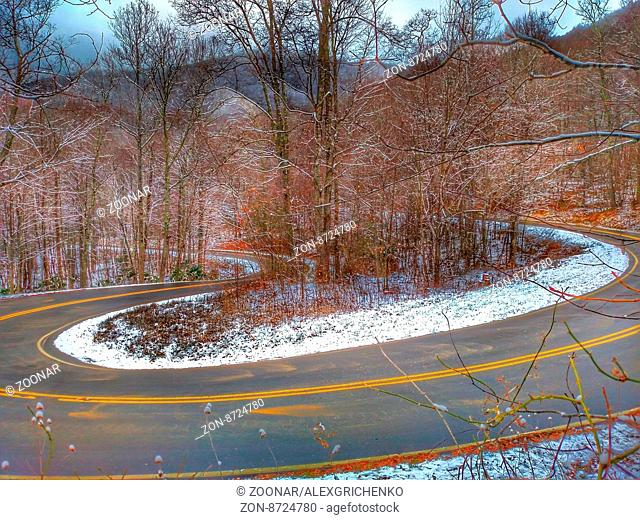 winding road through the mountains in winter