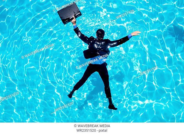Dressed businessman in swimming pool