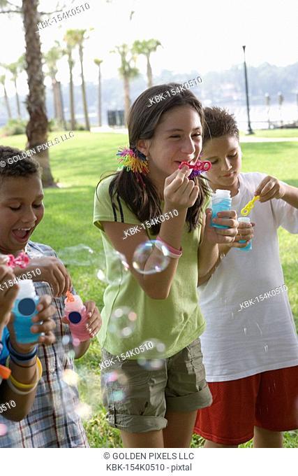Children blowing bubbles at a park