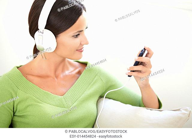 Horizontal portrait of an attractive woman using a portable music player while sitting indoors