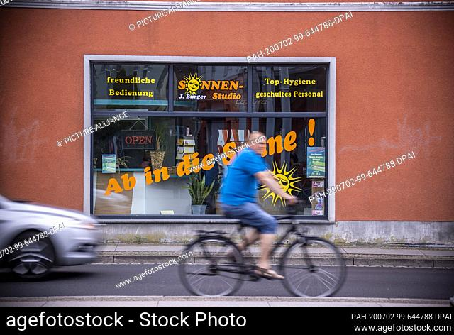 05 June 2020, Mecklenburg-Western Pomerania, Torgelow: Man rides his bike past a tanning salon. The small town, first mentioned in 1281, now has about 9
