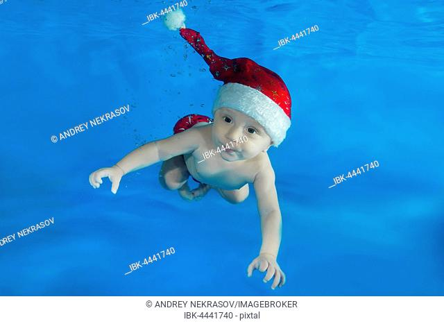 Baby, boy, in Santa's red cap swimming underwater in a pool, Odessa, Ukraine