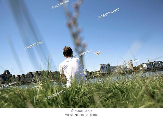 Mature man sitting in grass flying a drone