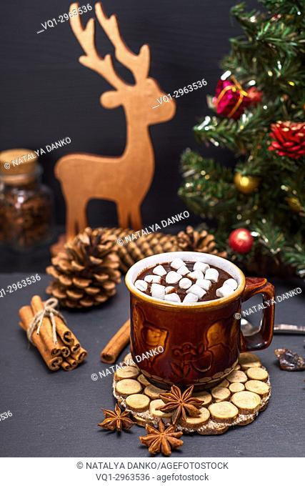 hot chocolate with marshmallow slices in a brown ceramic mug on a black background and Christmas decor