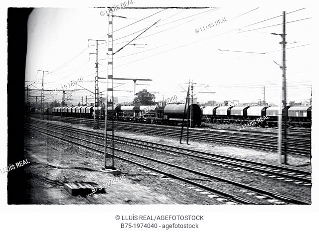 Station with trains, vagons, train tracks and telecommunications and electricity towers seen through the window of a train
