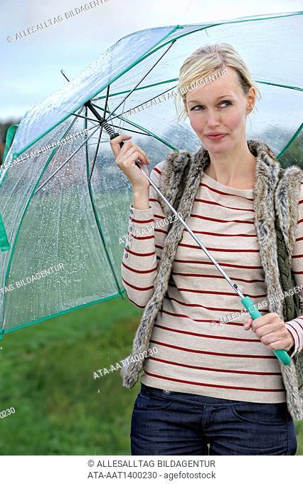 Woman walking in the rain with an umbrella
