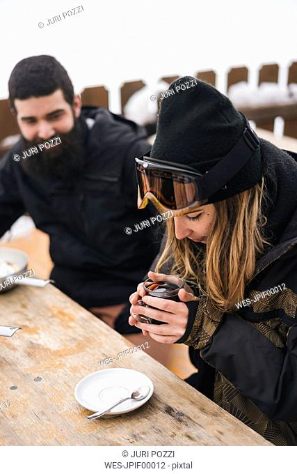 Couple in skiwear having a hot drink at mountain lodge