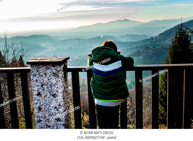 Boy looking out at mountain valley landscape from balcony, rear view, Piani Resinelli, Lombardy, Italy