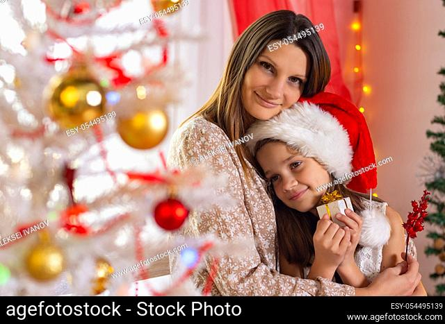 Girl holds Christmas gift, she is hugged by a happy mom