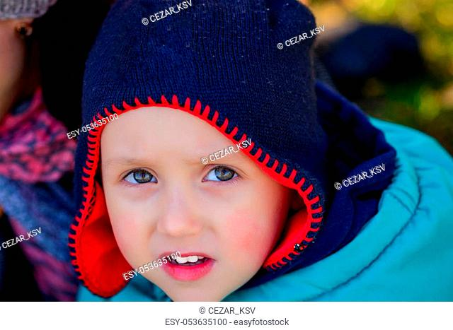 Close up of cute curious little boy with yellow leaf in a cap. Autumn concept