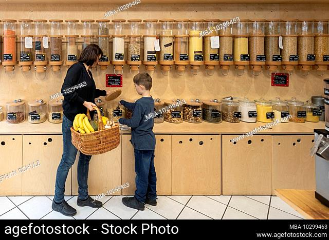 A woman and a boy are standing in front of a shelf with filling containers for grain in the packaging-free shop Frau Erna`s loser LebensMittelpunkt in Magdeburg