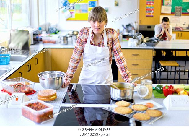 Portrait frustrated home economics teacher cooking in kitchen classroom with bored student