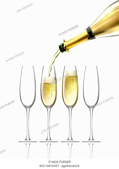 Gold champagne bottle filling four champagne flutes