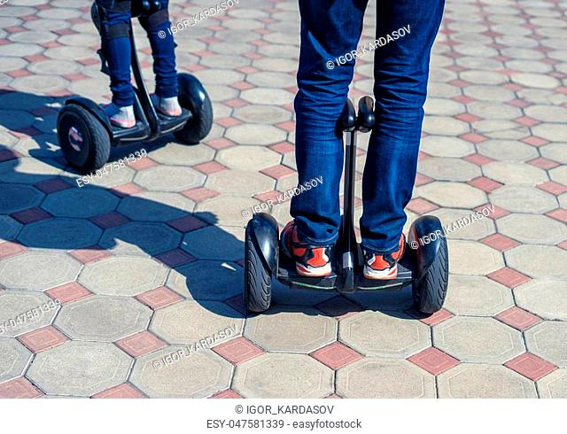 Young father teaching his daughter to ride electric mini hoverboard in park. Family concept
