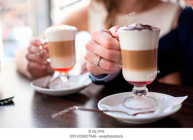 A man and a woman holding a cup of latte Women's and men's hands with wedding rings with two cups of coffee
