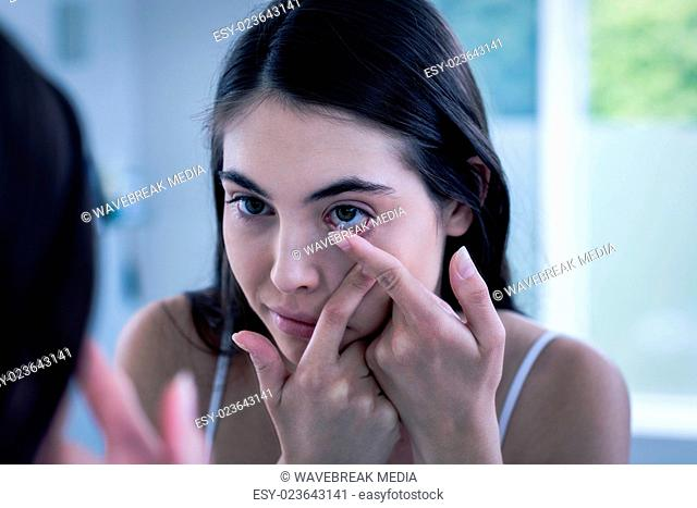 Brunette putting her contact lens