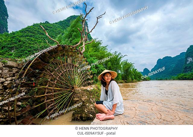 Woman with traditional straw hat resting at water wheel at the Yulong river in Guangxi, China
