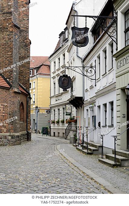 Street with restaurant signs in ancient Nikolaiviettel, Berlin