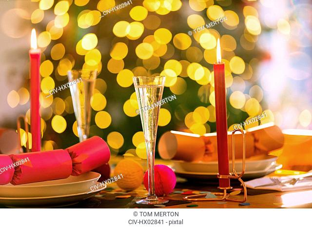 Champagne flutes, candles and Christmas crackers on dining table