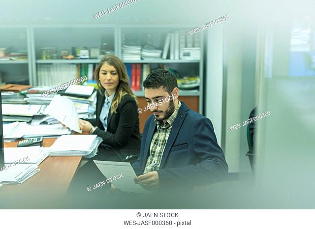 Young man and woman in office working on documents