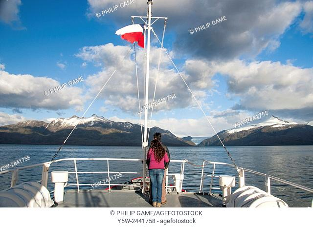 Young adult couple aboard MV Forrest on a whale-watching expedition cruise in the Straits of Magellan, Patagonia