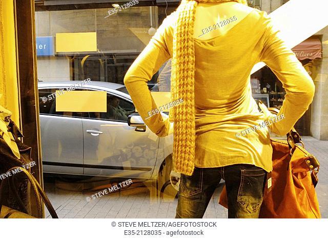 A female mannequin observes street traffic
