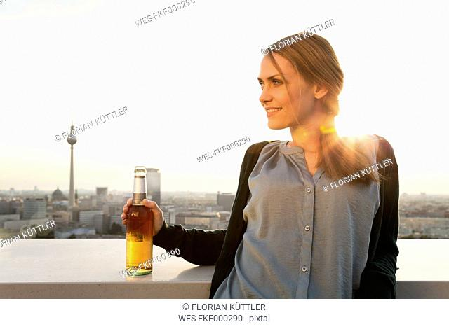 Germany, Berlin, Young woman on rooftop terrace, drinking beer
