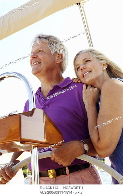 Mature couple standing in a boat and smiling