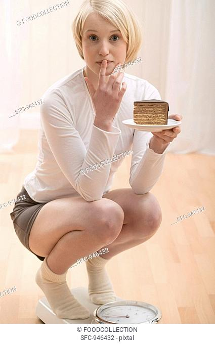 Young woman with a piece of cake on scales