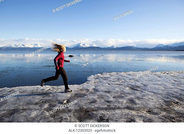 Woman running on the ice covered beach in Homer, Kenai Peninsula, Southcentral Alaska