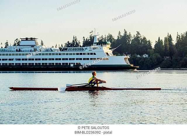 Caucasian man rowing on lake near cruise ship