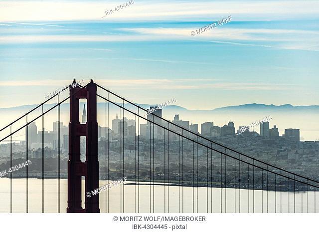 Golden Gate Bridge with skyline of San Francisco in the morning mist, California, USA