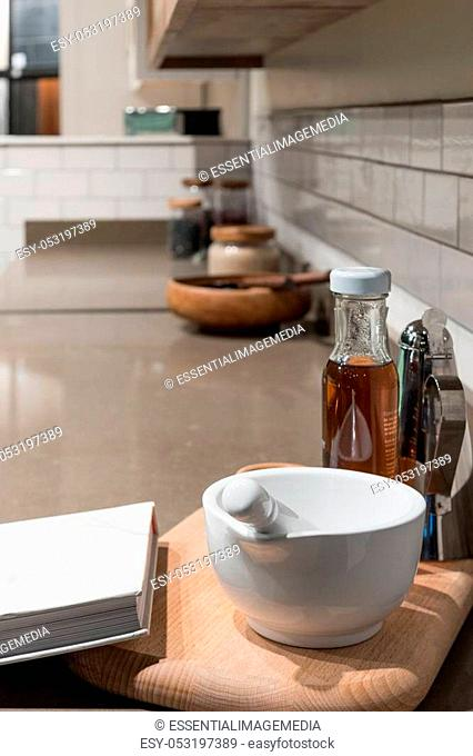 White Porcelain Pestle and Mortar Bowl with Assorted Cooking Accessories in Kitchen Scene