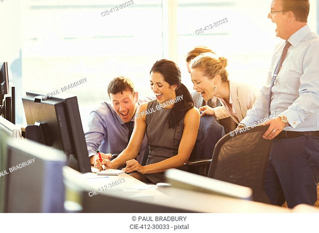 Business people laughing at desk in office