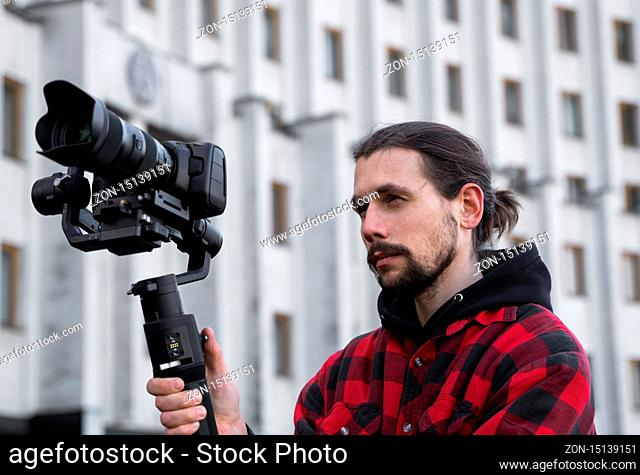 Young Professional videographer holding professional camera on 3-axis gimbal stabilizer. Pro equipment helps to make high quality video without shaking