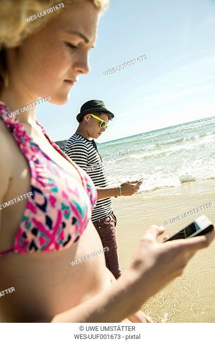 Teenage couple standing at waterside of the beach wearing using smartphones